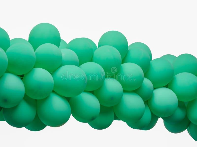 La couleur verte a décoré des ballons dans une rangée au-dessus du fond blanc image stock