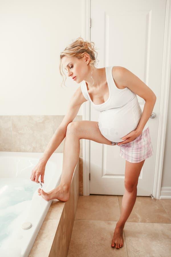 La coupe caucasienne blonde enceinte de femme épluchent des ongles de doigt sur des orteils de jambes dans la salle de bains photo stock