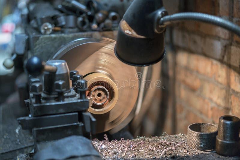 La coupe de machine de tour la tige en acier dans la scène bleu-clair La machine manuelle de tour avec la barre d'acier photos stock