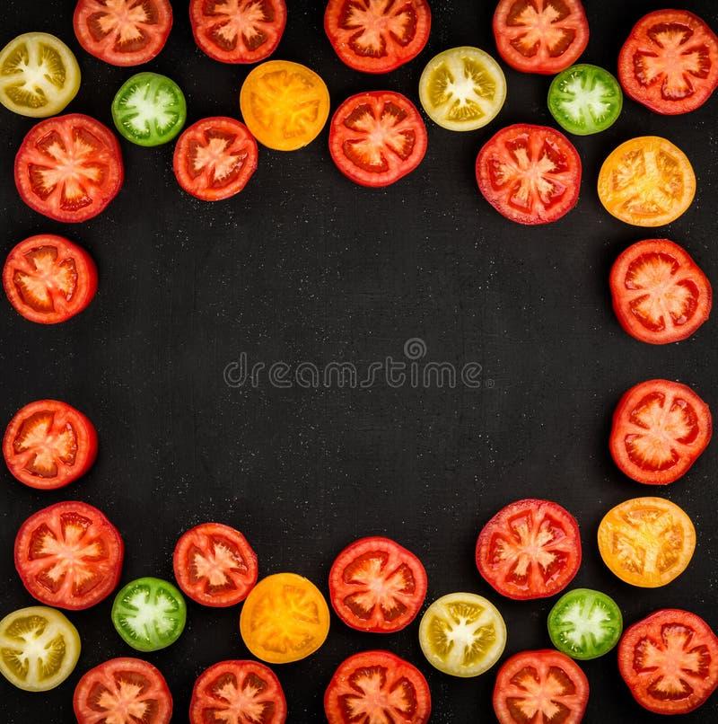 La coupe fraîche et juteuse de tomates dans la moitié a arrangé sous forme de frameon la table noire, fond végétal photo stock