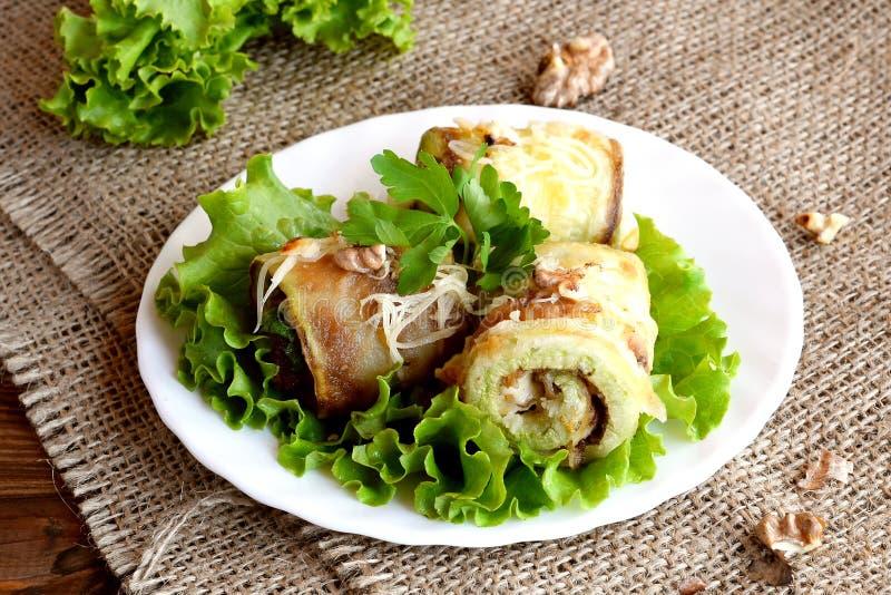 La courgette bourrée frite roule avec du fromage, les noix et le persil frais décorés de la laitue verte sur un plat photo libre de droits