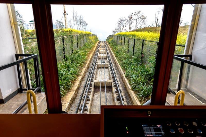 La course de tram par un gisement de fleur jaune prend des touristes jusqu'au dessus de la crête de montagne de Fansipan dans la  images libres de droits