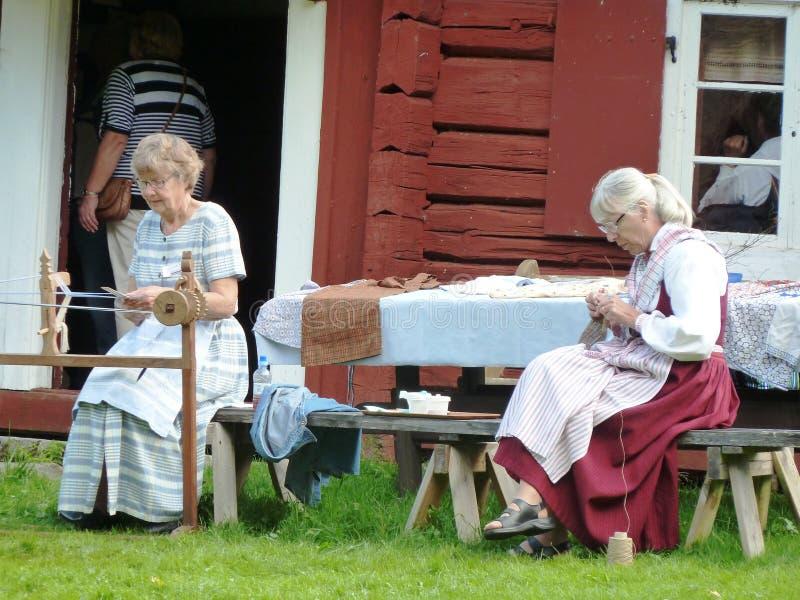 La couture de femmes s'est habillée dans de vieux costumes en dehors de vieille grange rouge en Suède photo libre de droits