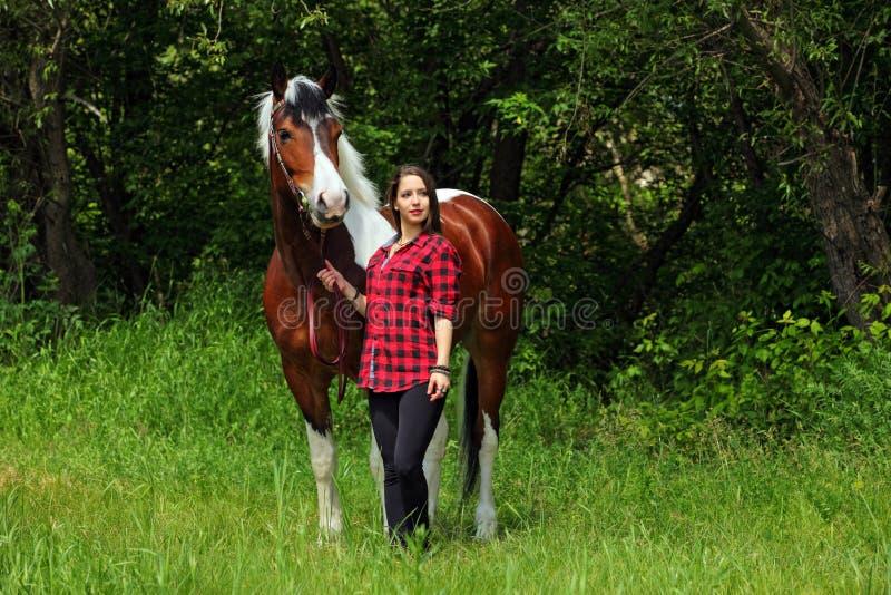 La cow-girl de sourire gaie marche cheval à cru images stock