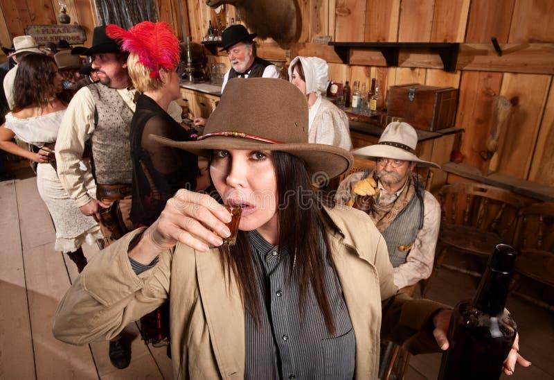 La cow-girl sirote le whiskey dans la taverne photographie stock libre de droits