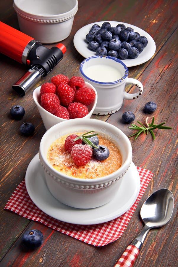La crème-brulée con le bacche e la vaniglia attaccano, primo piano immagini stock libere da diritti