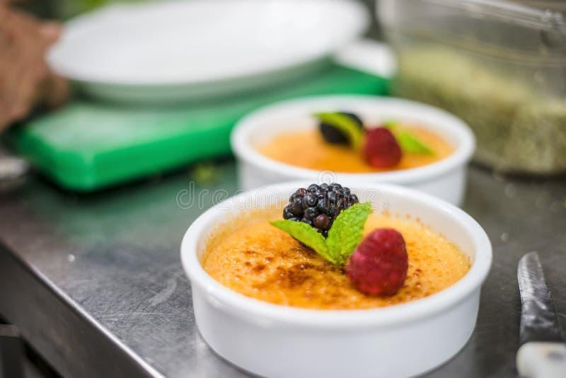 La crème Brule avec des fruits frais réunissent la feuille en bon état images libres de droits