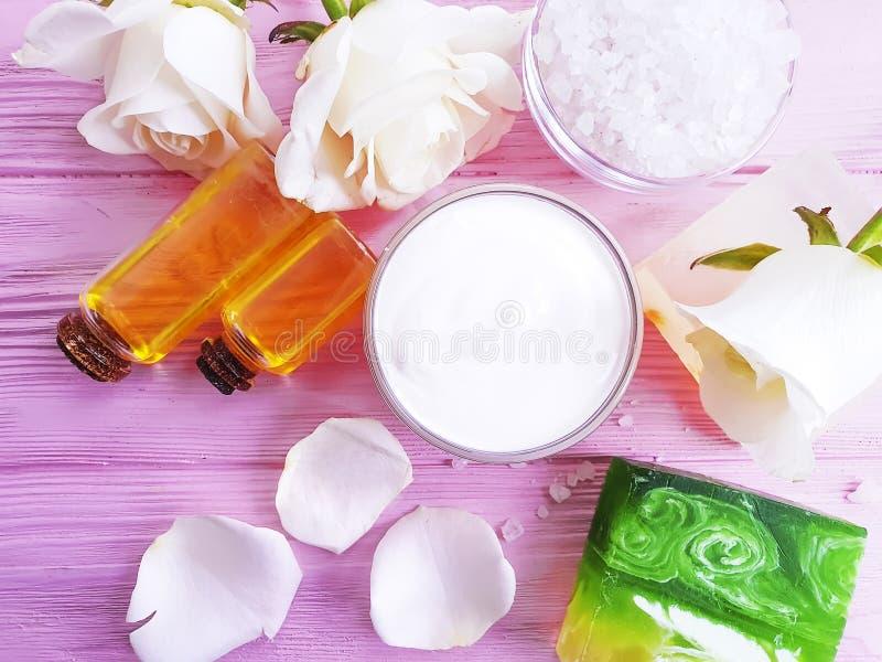 La crème cosmétique, extrait de crème hydratante s'est levée la fleur, savon sur un fond en bois rose photographie stock