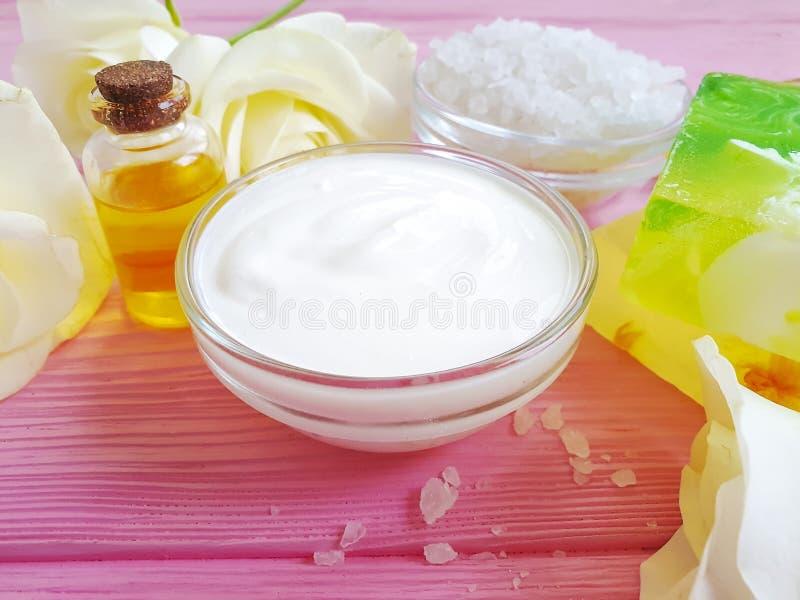 La crème cosmétique, extrait organique de crème hydratante s'est levée la fleur, savon sur un fond en bois rose images stock