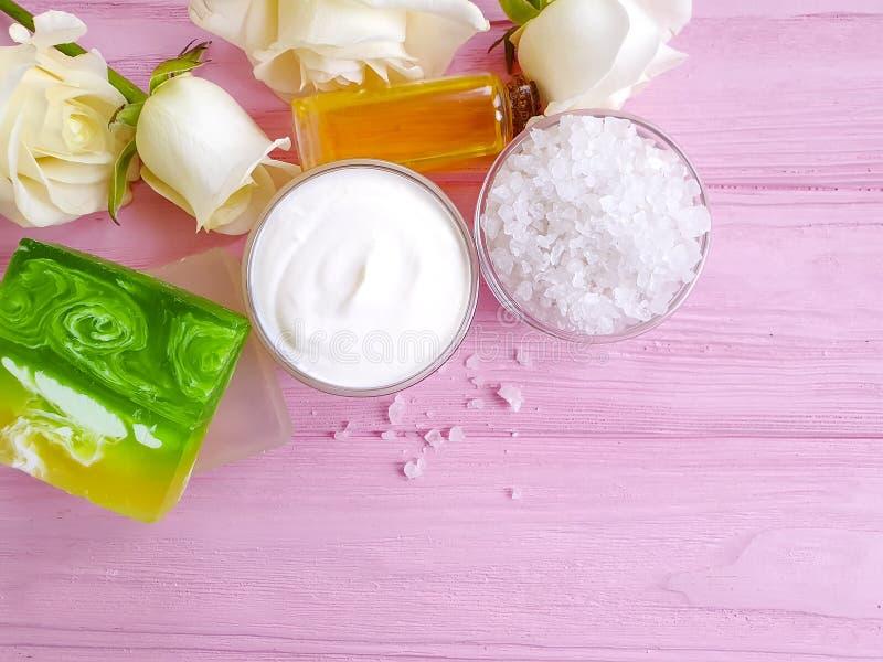La crème cosmétique, extrait organique de mode de vie de crème hydratante s'est levée la fleur, savon sur un fond en bois rose image libre de droits