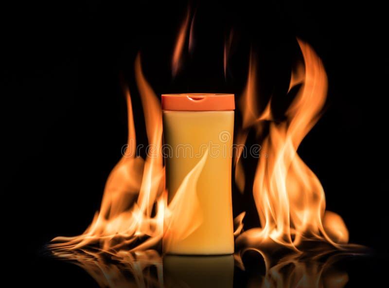 La crème de protection de Sun, lotion se tient dans un feu sur le fond noir photo libre de droits
