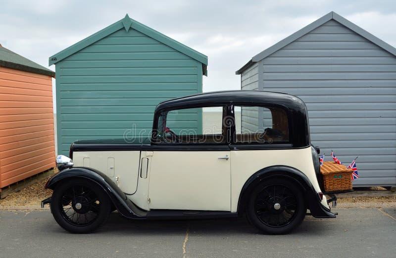 La crème de vintage et le noir Austin Seven Motor Car avec le panier se sont garés sur la promenade de bord de mer devant des hut photos libres de droits