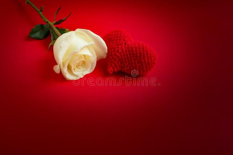 La crème s'est levée avec le crochet rouge de coeur sur le fond rouge images libres de droits