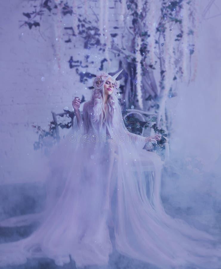 La création merveilleuse, la fille est une licorne dans la lumière, blanc, vêtement légèrement transparent Pièce légère de fond c photo libre de droits