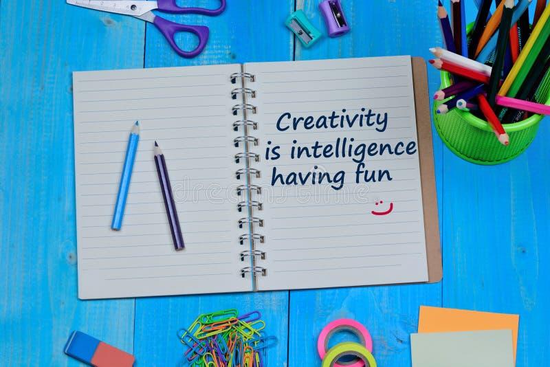 La creatività è intelligenza divertendosi il testo sul taccuino immagini stock
