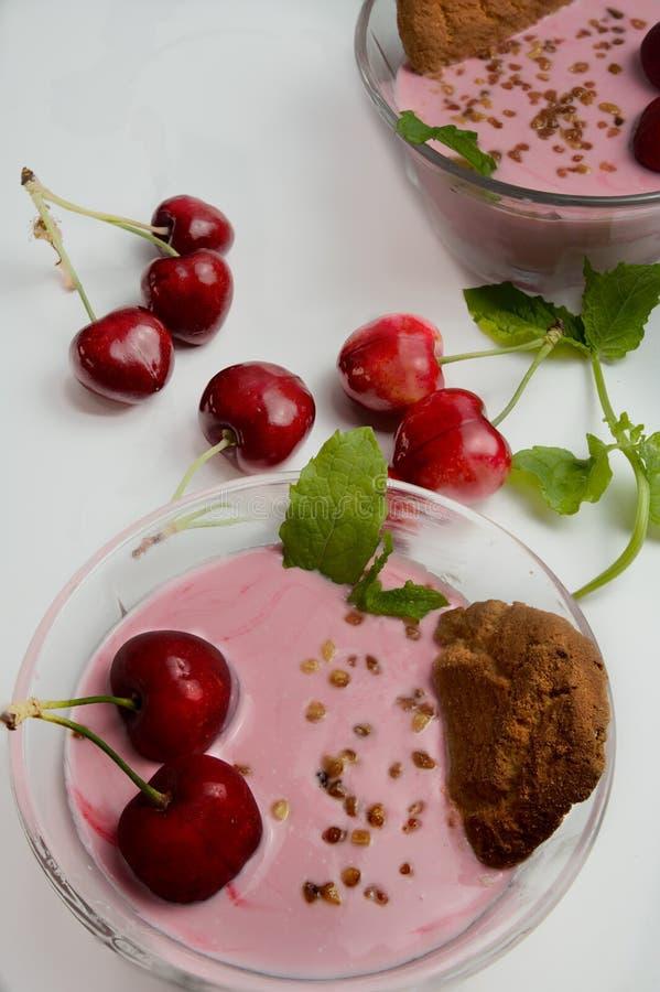 La crema batida fría de las cerezas sirvió con las cerezas frescas foto de archivo