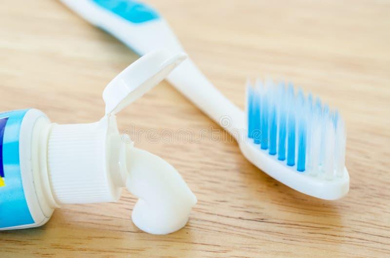 La crema dental blanca derrama hacia fuera un tubo de la crema dental y del cepillo de dientes fotos de archivo libres de regalías