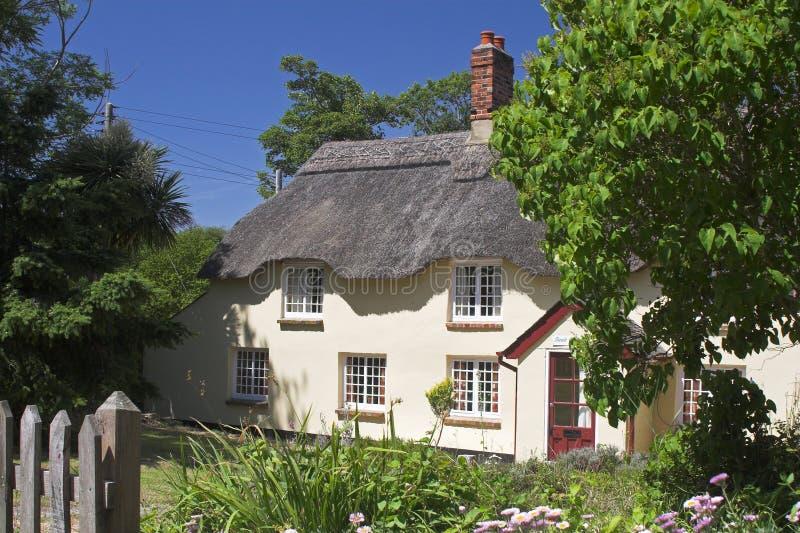 La crema thatched il cottage nella regolazione del giardino fotografia stock libera da diritti