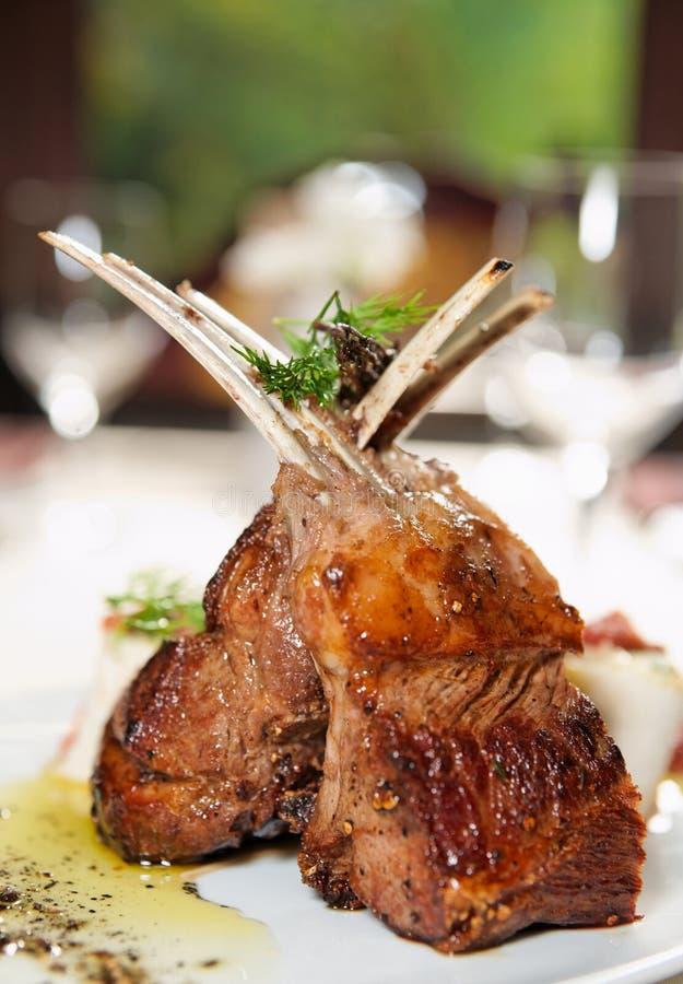 La cremagliera dell'agnello grezza ha fritto con le erbe e le spezie fotografia stock
