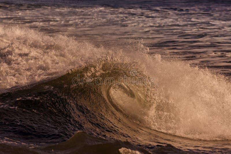 La cresta di un'onda che irrompe un tramonto immagine stock