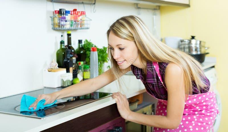 La criada limpia la estufa moderna foto de archivo libre de regalías