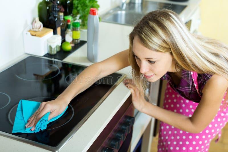 La criada limpia la estufa moderna imagenes de archivo