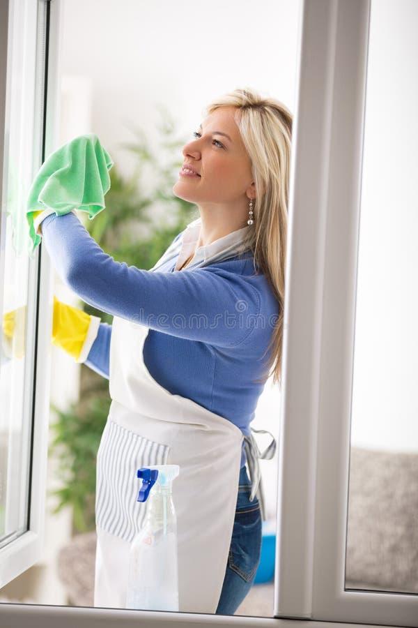 La criada limpia los vidrios de ventanas fotografía de archivo libre de regalías