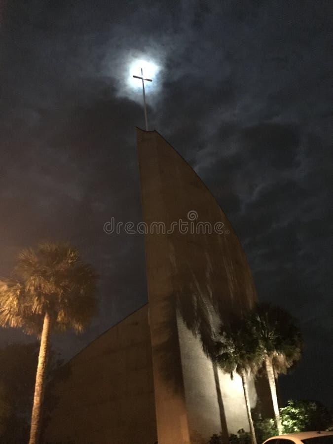 La croix de l'église semble s'allumer pendant que la pleine lune se montre de au delà des nuages images libres de droits