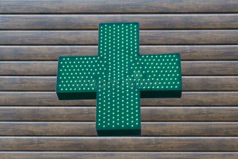 La croix verte au néon se connectent le fond en bois photo stock