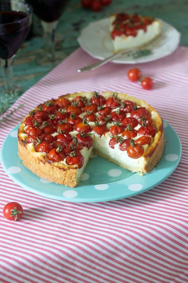 La crostata, la torta o la torta di formaggio con la ricotta ed i pomodori, sono servito con vino rosso su un fondo di legno fotografie stock