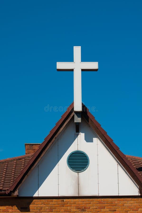 La cruz blanca sienta orgulloso en la azotea de la iglesia imagen de archivo libre de regalías