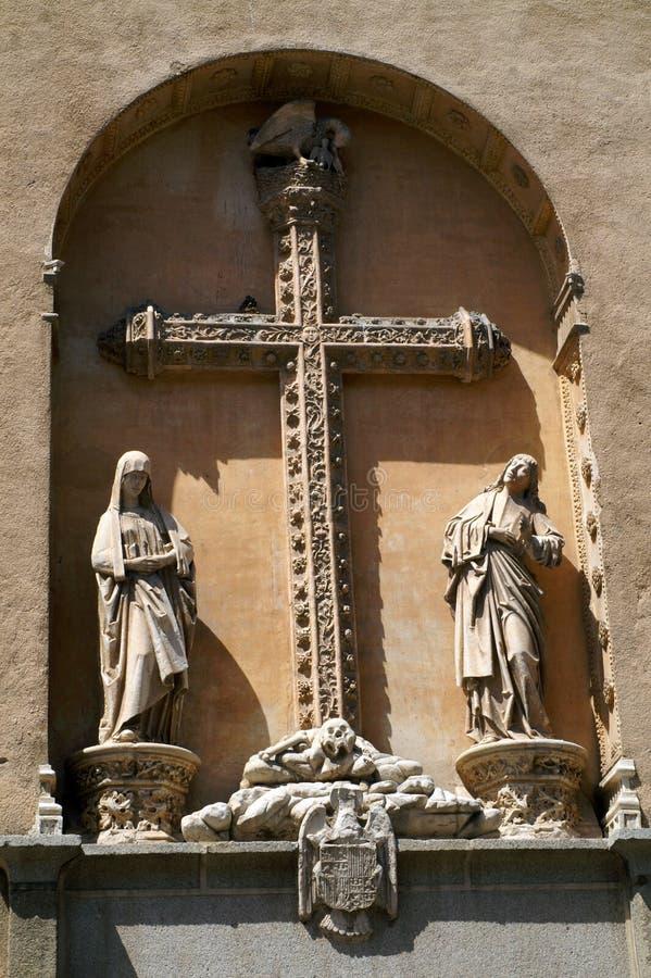 La cruz católica y dos figuras en el arco en la pared del edificio imagen de archivo