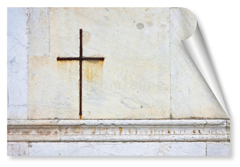 La cruz cristiana del hierro se acurrucó contra una piedra blanca en una iglesia italiana de la fachada - imagen del concepto de  fotografía de archivo