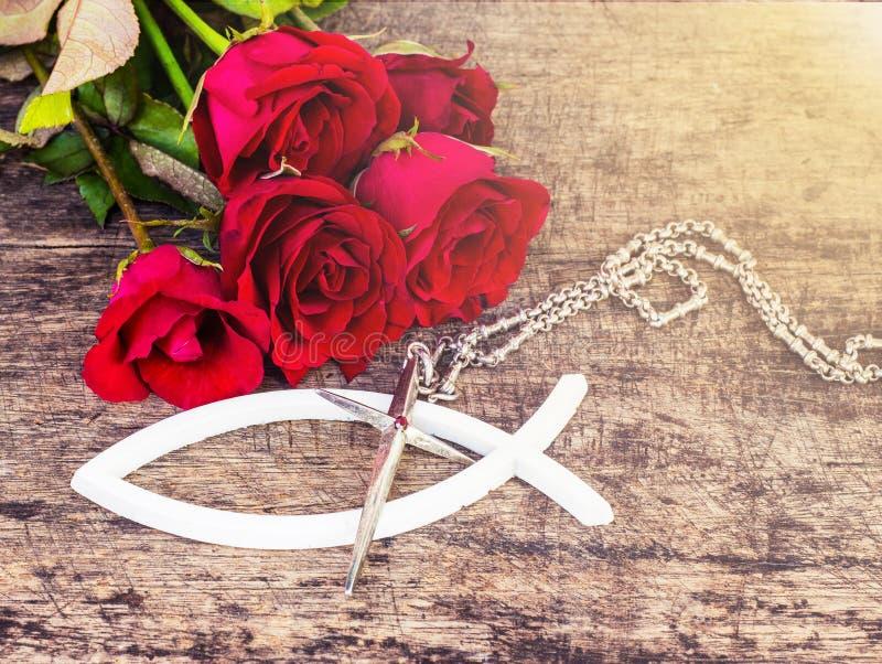La cruz del metal con las rosas rojas en la tabla de madera imagen de archivo libre de regalías