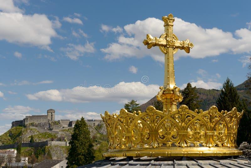 La cruz dorada del anuncio de la corona en Lourdes fotos de archivo