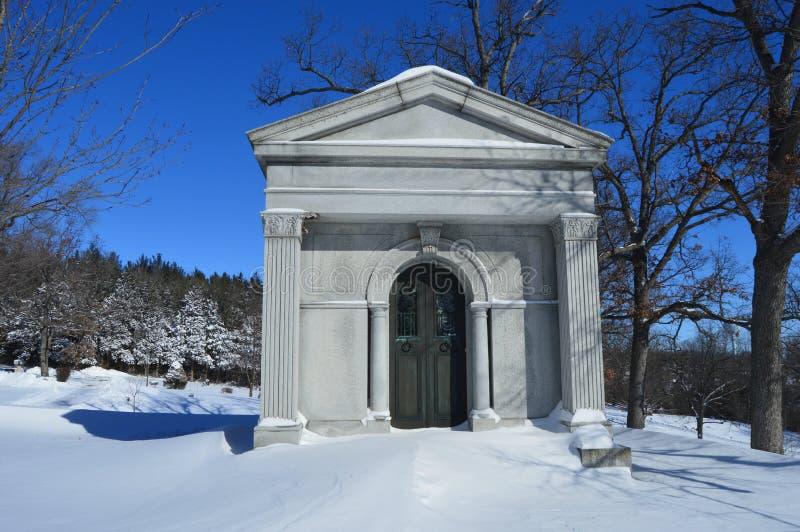 La crypte dans la neige a couvert le cimetière image stock