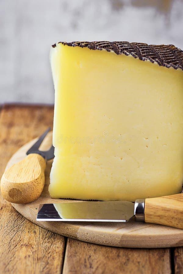 La cuña de la vaca de la cabra y del queso españoles de la oveja con negro texturizó la corteza en la tabla de cortar de madera B imágenes de archivo libres de regalías