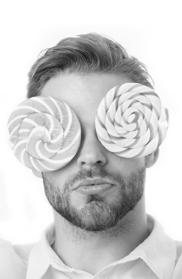 La cubierta barbuda del hombre observa con las piruletas aisladas en el fondo blanco Dulce como piruleta Divertirse con los caram foto de archivo libre de regalías