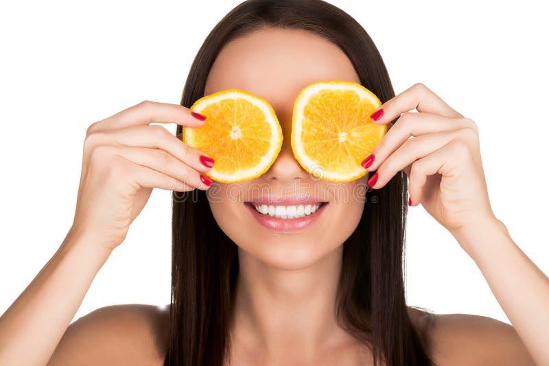 La cubierta de la mujer observa con la naranja cortada fotos de archivo libres de regalías
