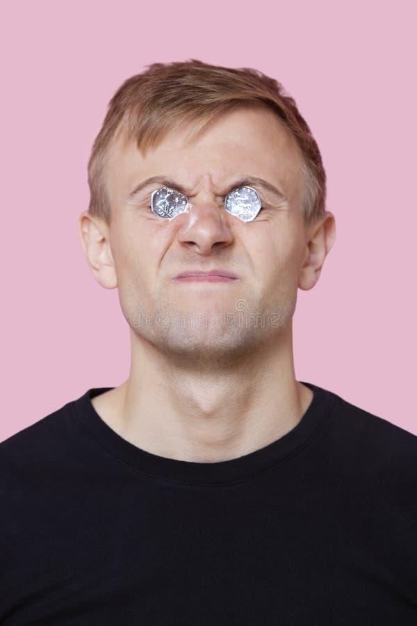 La cubierta divertida del hombre joven observa con las monedas sobre fondo rosado foto de archivo