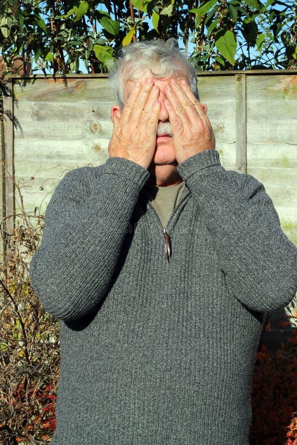La cubierta mayor del hombre observa con sus manos. foto de archivo libre de regalías