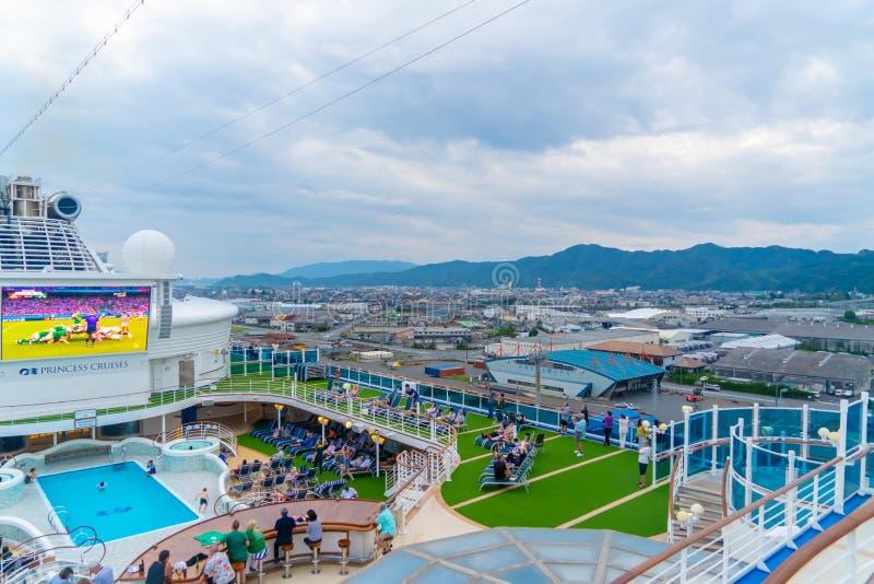 La cubierta superior del crucero Diamond Princess con gran TV LED y piscina foto de archivo libre de regalías