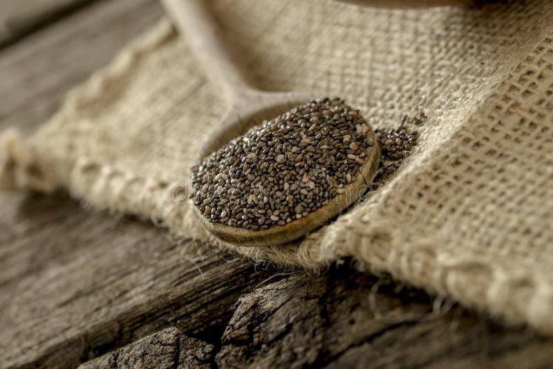 La cuchara de madera del chia siembra por completo la mentira en una materia textil de lino imagen de archivo
