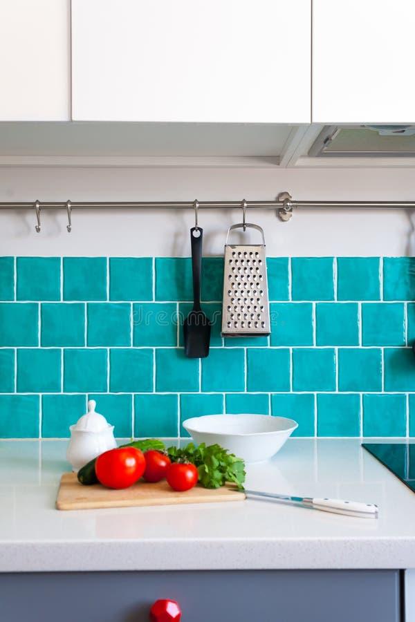 La cucina caratterizza i gabinetti anteriori piani grigio scuro accoppiati con i controsoffitti bianchi del quarzo e le mattonell immagine stock libera da diritti