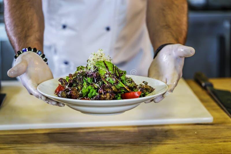 La cucina del ` s del ristorante, cuoco unico tiene un piatto, il foie gras, verdure, fotografia stock