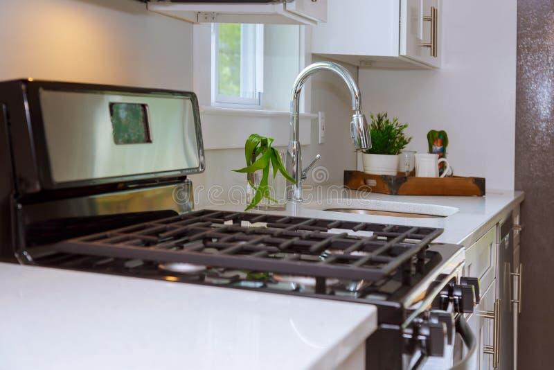 La cucina piacevolmente ritoccata con i ripiani lucidi del granito ha accoppiato con i gabinetti bianchi e gli apparecchi moderni immagine stock libera da diritti
