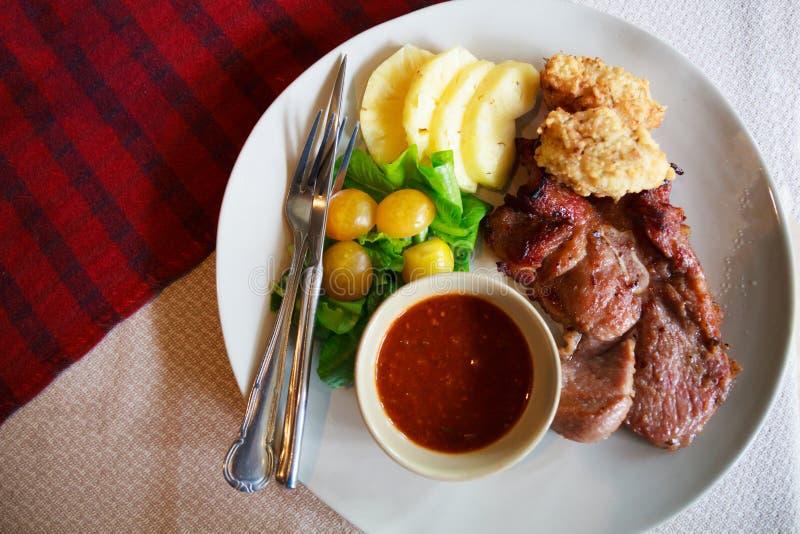 La cucina tailandese, bistecca della carne di maiale con riso appiccicoso in profondità infornato ha immerso con il pomodoro dell fotografie stock