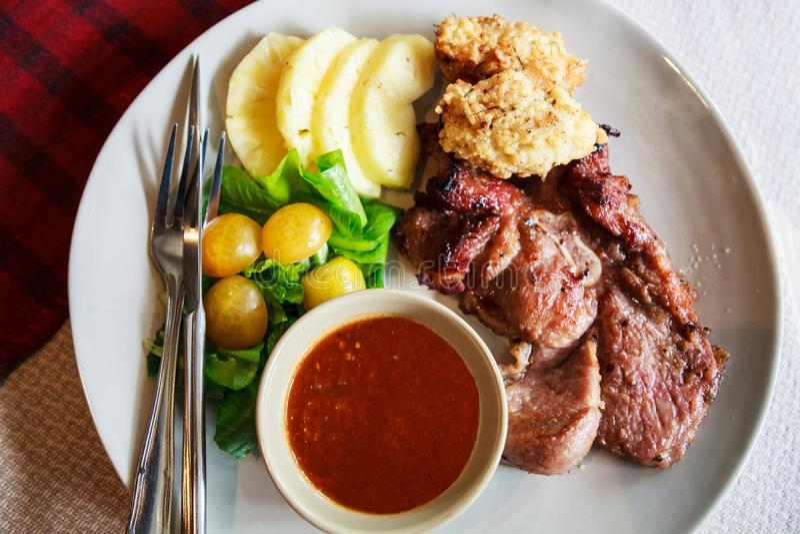 La cucina tailandese, bistecca della carne di maiale con riso appiccicoso in profondità infornato ha immerso con il pomodoro dell fotografia stock libera da diritti