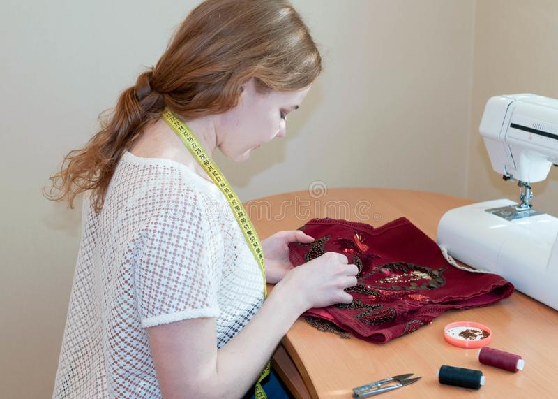 La cucitrice che si siede alla tavola con la macchina per cucire e ricama la maglia rossa in studio fotografia stock libera da diritti