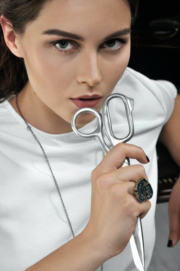 La cucitrice della ragazza tiene le forbici in sua mano immagine stock